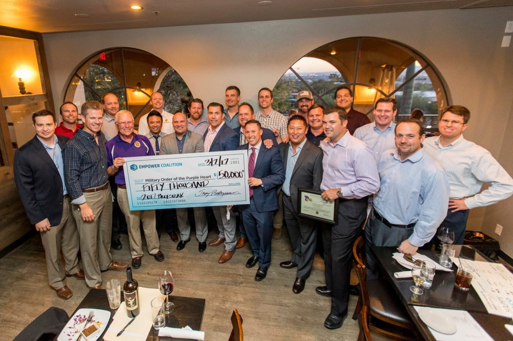 Members of Empower Coalition present Bob Asbell of Military Order of the Purple Heart with a check for $50,000 from the 2017 Tucson Beefsteak